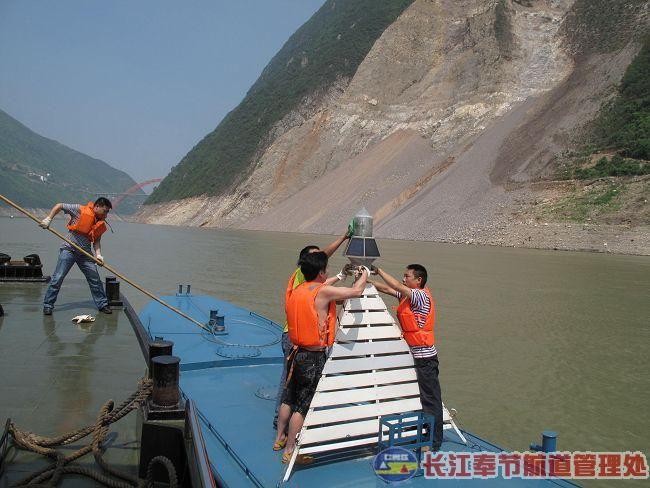 Workers from the Chongqing Waterway Bureau install a buoy near the site of the landslide across from Gongjiafang Village  in Wu Gorge. (Photo from the Internet).