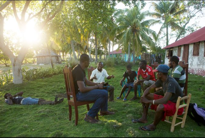 Members of KOPI, a grassroots organization made up of four local groups to press the Haitian government for transparency and community participation in its development plans for the island of Ile-a-Vache, Haiti, meet together on the island. Allison Shelley/The GroundTruth Project