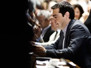 Alexis Tsipras, Greece's prime minister, reads documents after arriving at the Greek parliament to address lawmakers in Athens, Greece, on Friday, July 10, 2015. In an 11th-hour bid to stay in the euro, the government of Tsipras offered to meet most of the demands made by creditors in exchange for a bailout of 53.5 billion euros (US$59.4 billion). Kostas Tsironis/Bloomberg.