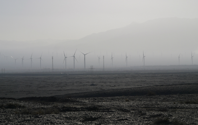 Goldwind's newest turbines at Dabancheng stand still, amid a sandstorm. The reason they're not spinning? China hasn't yet installed enough grid capacity to accommodate their energy. (Rob Schmitz/Marketplace)