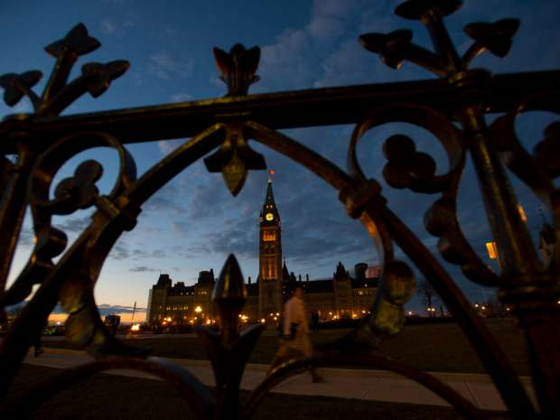 The sun sets behind Parliament Hill in Ottawa. The Canadian Press/Sean Kilpatrick.